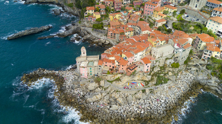 Aerial shooting with drone on Tellaro, famous Ligurian village near the Cinqueterre, small colored houses built on the cliff by the sea