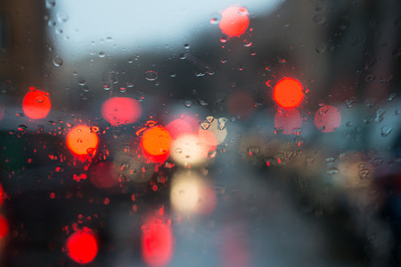 blurred light of cars seen through a wet windshield with some raindrops Stock fotó