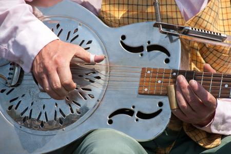 Street guitarist playing a metallic guitar called dobro Banco de Imagens