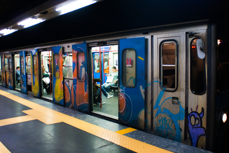 A Subway car painted by graffiti writers  at station with opened doors