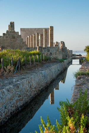 oasis at sunrise: Ruins of an old plant for tuna fishing and processing at dawn with reflection on still sea in nature reserve of Vendicari in south-eastern Sicily Stock Photo