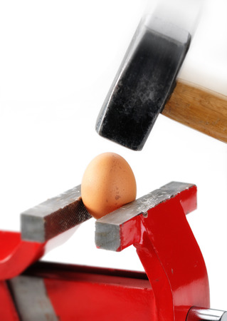 An egg gripped in the vise while a big and heavy hammer is almost hitting it photo