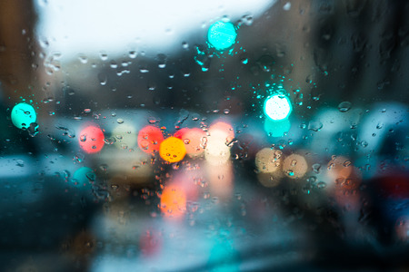 blurred light of cars seen through a wet windshield with some raindrops Stok Fotoğraf