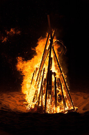 A pyre burning in the night on a beach