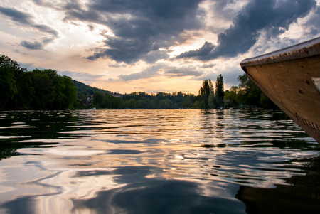 rhein: Wooden boat navigating on the still water of Rhine river at sunset with trees on background