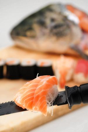 Paradoks: Sushi na knurów cięcia, z głową i łososia na tle jakiegoś łososia sashimi serwowane na ostrze noża na pierwszym planie Zdjęcie Seryjne