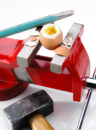 An egg gripped in the vise broken by a chisel, hammer and pieces of broken eggshell are around photo
