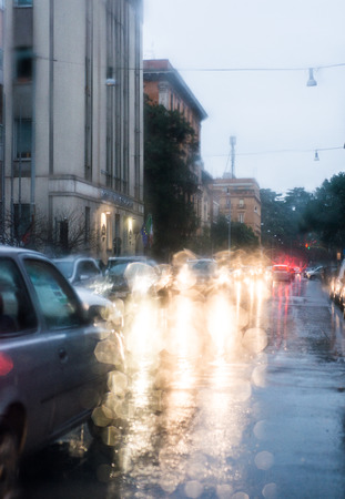 blurred light of cars seen through a wet windshield with some raindrops photo