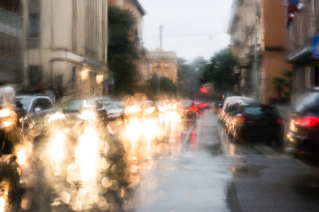 blurred light of cars seen through a wet windshield with some raindrops Banco de Imagens