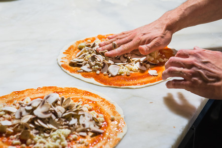 woodfired: Pizza chef spreading out and garnishing a delicious pizza