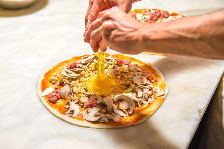 Pizza chef spreading out and garnishing a delicious pizza