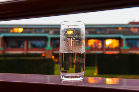glass of water on the edge of a balcony of a hotel room, on the background blurred lights at dusk