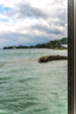 blurred view of the lake seen through a window with sharp drops on a rainy day