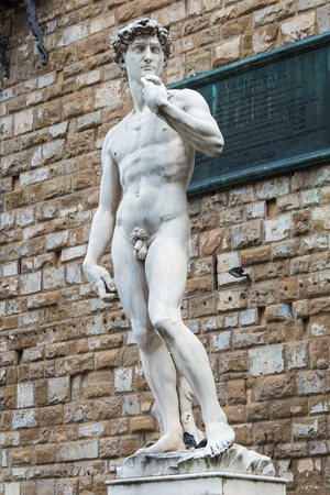 A copy of the statue of David by Michelangelo, in the background of the Palazzo Vecchio in Piazza della Signoria in Florence