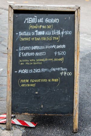 on a restaurant menu written on a blackboard in the middle of a street in the center of Florence