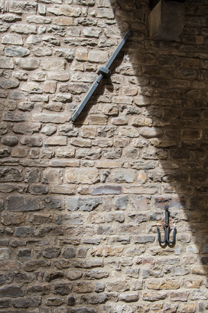 Ancient medieval stone wall of the house where Dante Alighieri  was born in the center of Florence with iron inserts and hooks