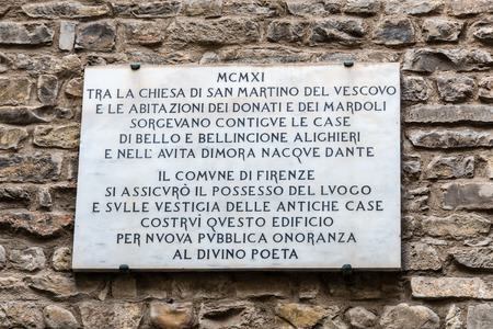 Ancient medieval stone wall of the house where Dante Alighieri  was born in the center of Florence with memorial plaque with inscription