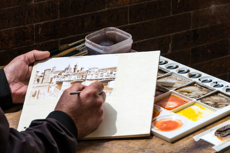 Detail of the hands and tools of a street artist who paints Ponte Vecchio in Florence, warm colors