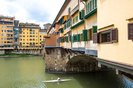 Glimpse of Arno River at Ponte Vecchio in Florence with typical houses and canoes in the water on a cloudy day Stock fotó
