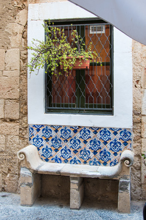 Marble bench on a stone wall with painted tiles under a barred window and plant. Syracuse, Ortiggia, Sicily, Italy Stock fotó