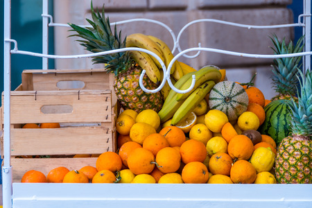 Cart with boxes of oranges, lemons, melons, watermelon, pineapple and bananas against a wall in Syracuse, Sicily, Italy