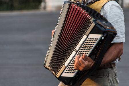 limosna: M�sico callejero tocando un acorde�n limosna al atardecer en Siracusa, Ortigia, Sicilia, Italia Foto de archivo