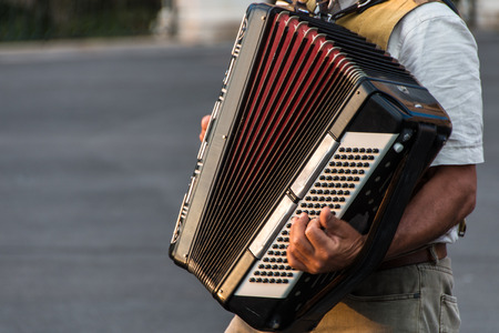 Street musician playing an accordion for alms at sunset in Syracuse, Ortigia, Sicily, Italy Banco de Imagens