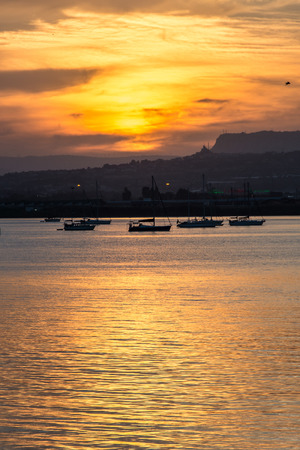 Orange sunset over the sea of Syracuse, Ortigia, Sicily, Italy, with moored boats and mountains on the horizon. Vertical shot.