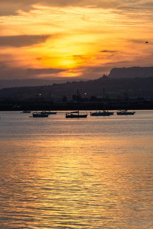 ortigia: Orange sunset over the sea of Syracuse, Ortigia, Sicily, Italy, with moored boats and mountains on the horizon. Vertical shot.