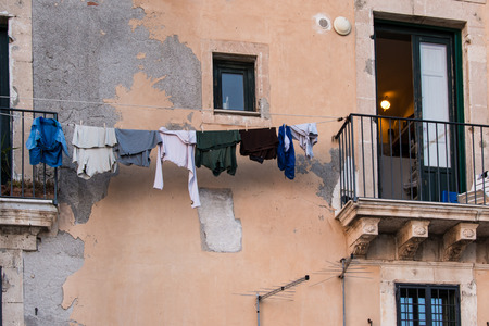 Laundry hanging to dry on a wire with the clothespins against the badly damaged facade of a house in Ortigia, Siracusa, Sicily, Italy