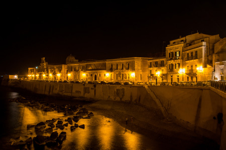 Panorama Syracuse, Ortiggia, Sicily, Italy, houses facing the sea in the night, in the background of dark black sky, reflections on the sea and street lamps