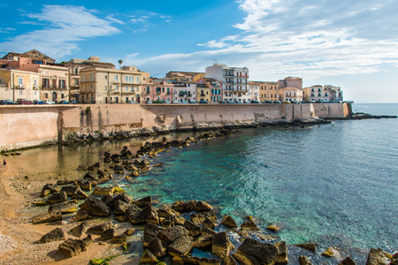 Panorama Syracuse, Ortiggia, Sicily, Italy, houses facing the sea in the morning, in the background of blue sky and reflections on the sea