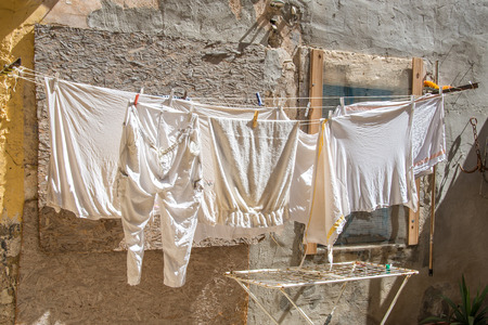 ortigia: Laundry hanging to dry on a wire with clothespins against the badly damaged the facade of a house in Ortigia Syracuse Sicily Italy