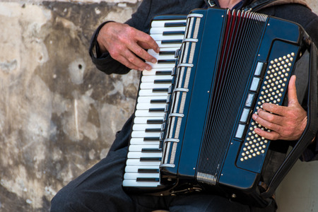 Street musician playing an accordion for alms at sunset in Ortigia Syracuse Sicily Italy Banco de Imagens