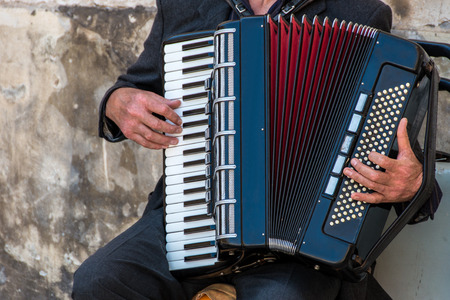 Street musician playing an accordion for alms at sunset in Ortigia Syracuse Sicily Italy Stock Photo