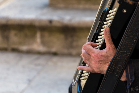 Street musician playing an accordion for alms at sunset in Ortigia Syracuse Sicily Italy Stock fotó