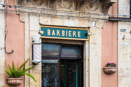 palazzolo: Barber sign with rotating pole and flowers in Palazzolo Acreide Siracusa Sicily Italy
