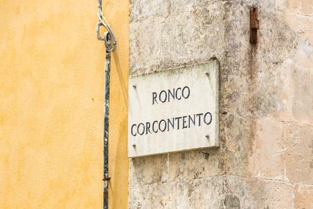 palazzolo: Marmo targa con il nome della strada su giallo muro intonacato con una parte rivestita di marmo a Palazzolo Acreide Siracusa Sicilia Italia