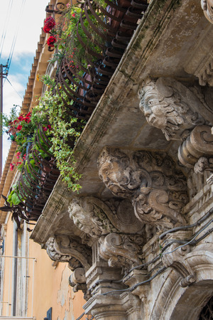 Balcony with iron railing with marble capitals and friezes baroque. Syracuse Sicily Italy