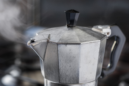 Italian traditional coffeemaker with hot steam blowing out from the spout