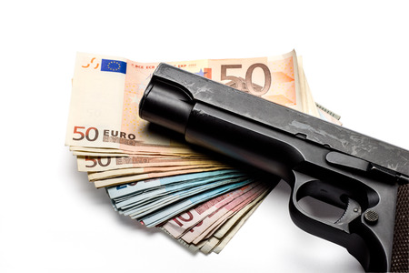 Bunch of euro banknotes of various denominations with a gun. Isolated on white