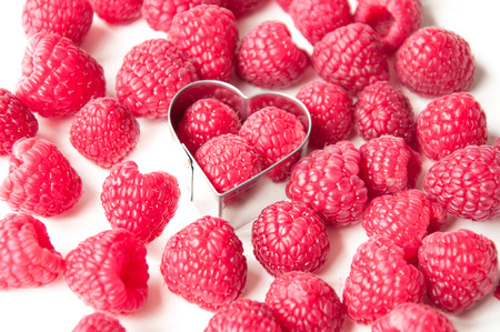 beautiful pink raspberries in a metal heart on a white background with other raspberries photo