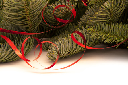 green fir-tree twigs with red ribbons on a white background Stock Photo