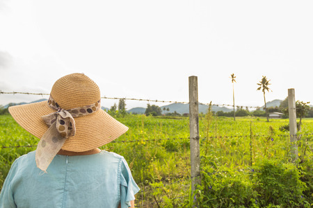 Woman with large sun hat looking the view of countryside through barb wire fence