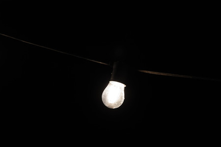 Single glowing light bulb hanging on black cable with black background