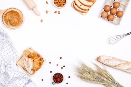 Panes caseros o bollo, croissants e ingredientes de panadería, harina, nueces de almendras, avellanas, huevos sobre fondo blanco, marco de fondo de panadería, concepto de desayuno de cocina. Endecha plana, vista superior y espacio de copia.
