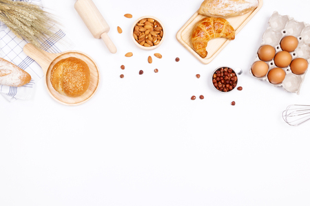 Homemade breads or bun, croissant and bakery ingredients, flour, almond nuts, hazelnuts, eggs on white background, Bakery background frame, Cooking breakfast concept. Flat lay, Top view and copy space