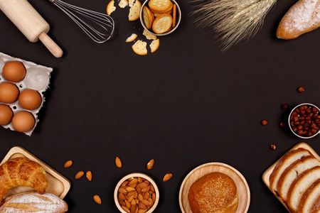 Homemade breads or bun, croissant and bakery ingredients, flour, almond nuts, hazelnuts, eggs on dark background, Bakery background frame, Cooking breakfast concept. Flat lay, Top view and copy space.