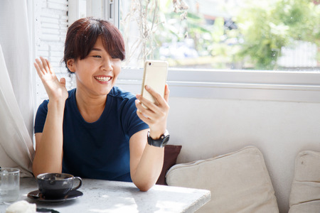 Young female talking with her friend on smartphone device.  Copy space.