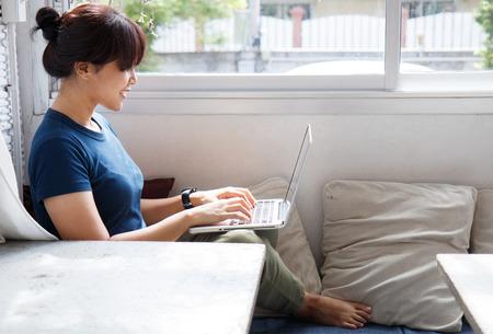 Lachende vrouw kijken naar video op laptopcomputer in gezellige naaiatelier interieur, vrouwelijke student rust tijdens de vrije tijd lezen van nieuws bloggen in sociale netwerken met behulp van netbook. Stockfoto